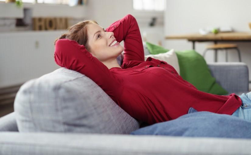 zufriedene frau lehnt sich auf dem sofa zurück